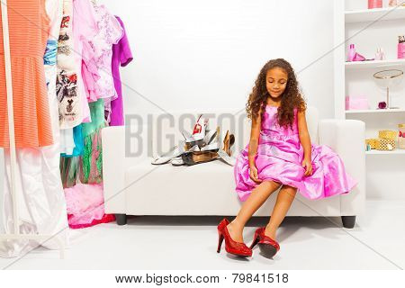 Little African girl trying on mothers shoes