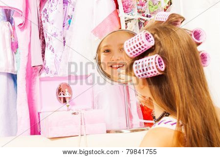 Smiling cute girl making up her face with lipstick