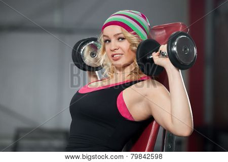 Female Trains In Gym With Dumbbells