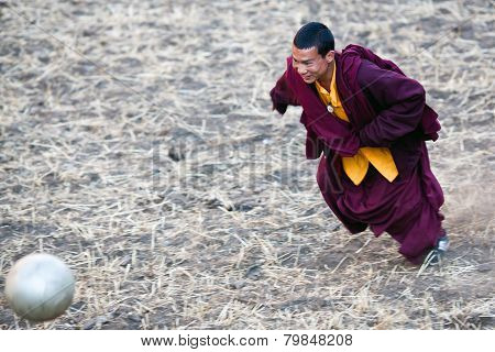 Monk playing soccer, Nepal