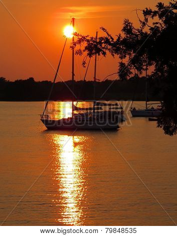 Sailboat In The Sunset On A Lake