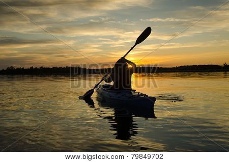 Woman Kayaks At Sunset