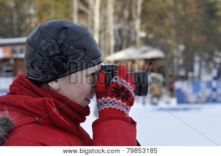 The Woman In Winter Clothes Photographs The Slr Camera.