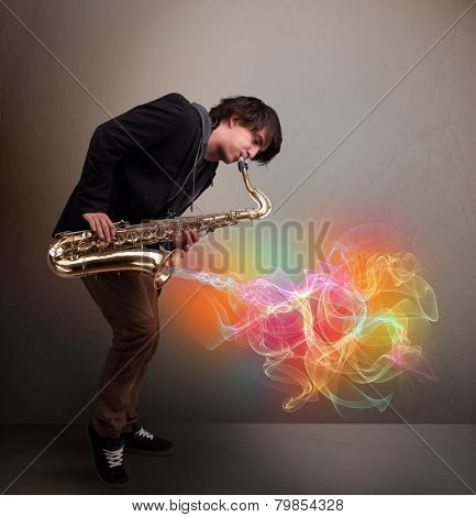 Attractive young musician playing on saxophone with colorful abstract fume comming out