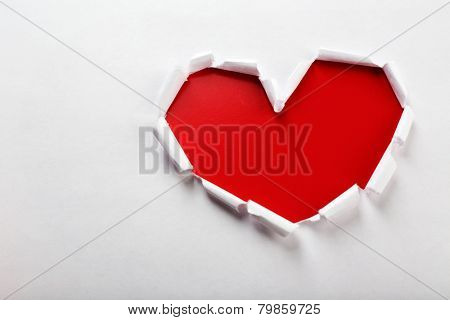 White torn paper heart over red background
