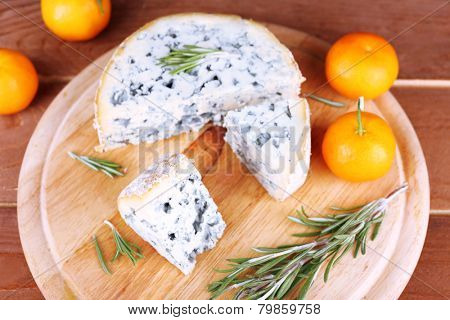 Blue cheese with sprigs of rosemary and oranges on board and wooden table background