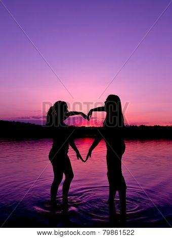 Two Young Girls Make The Shape Of Heart