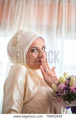 Shy muslim girl smiling with flowers in her hands