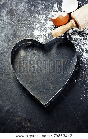 baking background with raw eggs, rolling pin, flour and heart shape cookie cutter