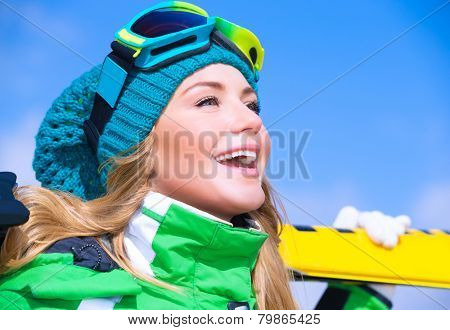 Closeup portrait of cute happy skier girl on blue sky background, extreme winter sport, active lifestyle concept