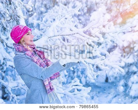 Portrait of cute happy girl enjoying winter, having fun outdoors, catches snowflakes by hands, happiness and activity in wintertime