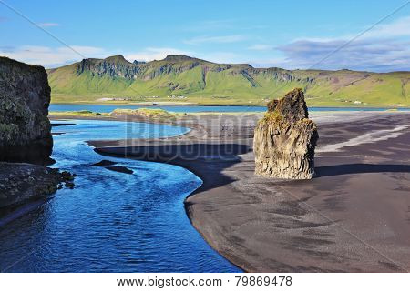 Rock in the sand. Cape Dirholaey in southern Iceland. On the beach with black volcanic sand is a huge rock
