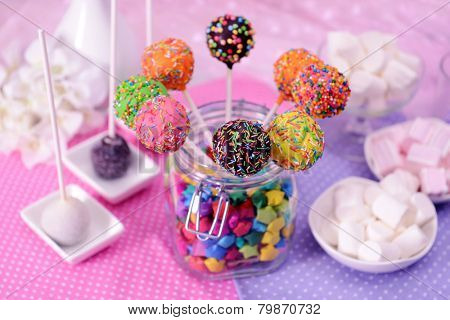 Sweet cake pops in jar on table on bright background
