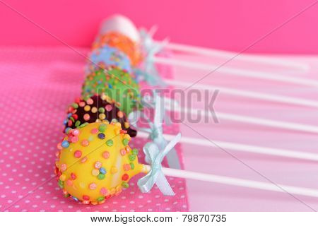 Sweet cake pops on table on pink background