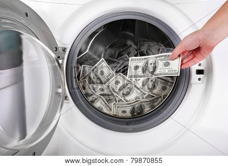 Female putting money into washing machine, closeup