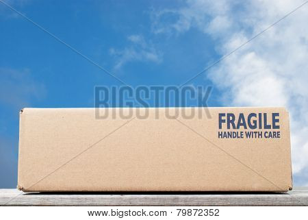 Shipping Box With Fragile Handle With Care As Notice Against Blue Sky Background