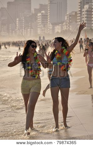 Two happy young women enjoy Carnival in Ipanema beach