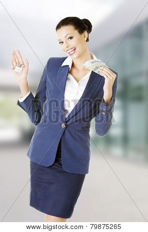 Beautiful young business woman with money and keys