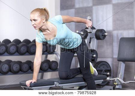 Attractive blond sporty girl doing triceps training with a dumbbell