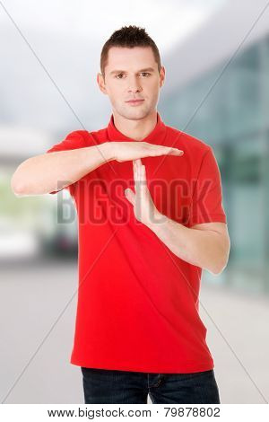 Handsome man showing time out sign with hands