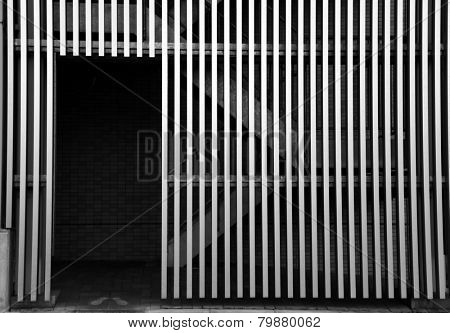 Open door and grill wall in monochrome