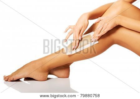 Spa woman waxing her leg
