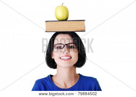 Portrait of a woman holding book and apple on head.