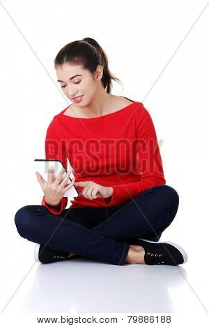 Student woman sitting cross-legged using a tablet.