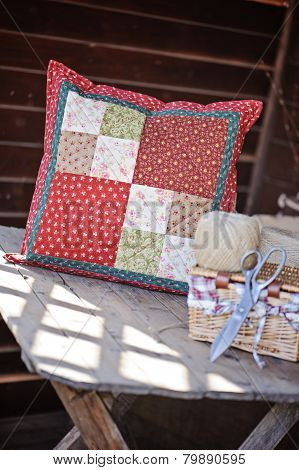 handmade patchwork cushions with sewing tools on wooden table