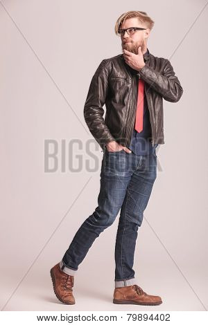 Fashion man walking on studio background holding one hand in his pocket while fixing his beard and looking away from the camera.