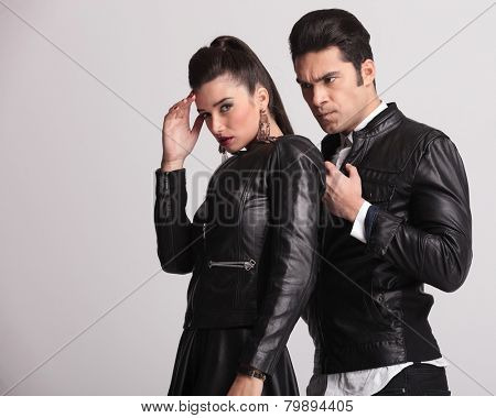 Side view of a fashion couple posing against studio background. The woman is holding her hand to her head, looking at the camera while her boyfriend is looking away.