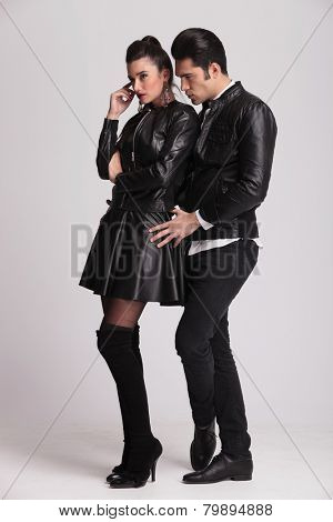 Full body picture of a fashion couple standing on grey studio background.The man is holding the woman by her hips while looking down.
