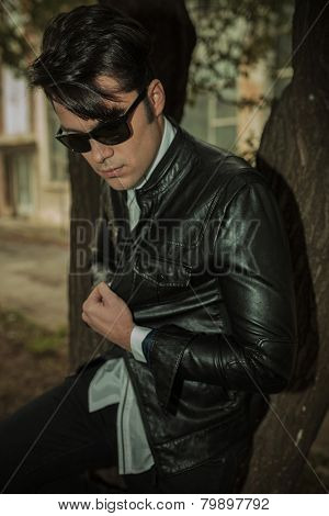 Portrait of a young casual man looking down while leaning on a tree, pulling his jacket.