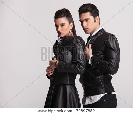 Fashion woman looking away while unzipping her leather jacket. Her lover is standing behind her, fixing his jacket.
