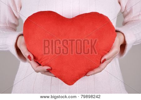 Woman holding a plush red heart
