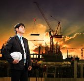 foto of land development  - engineering man and safety helmet standing against crane constructiion in building site use for construction industry business and land development topic - JPG
