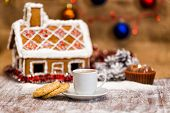 stock photo of gingerbread house  - cup of coffee and oatmeal cookies on a background of traditional gingerbread house - JPG