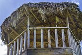 stock photo of tiki  - The roof of a tiki hut tower with blue sky in the background - JPG