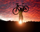 picture of exercise bike  - Mountain biker silhouette against the sunset concept for achievement - JPG
