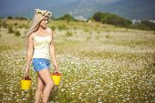 stock photo of bucket  - Young blonde woman with green eyes, long flowing hair on his head wearing a wreath of flowers camomile in the hands - a bucket of strawberries and a bucket of cherries, a white T-shirt and blue shorts.