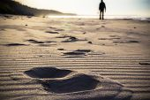 stock photo of footprint  - Footprint in the sand and the figure of a man cultivating Nordic walking - JPG
