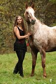 foto of appaloosa  - Beautiful girl with nice dress standing next to nice horse in autumn - JPG