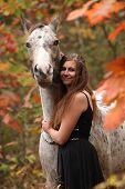 foto of appaloosa  - Pretty young woman with appaloosa horse in autumn - JPG