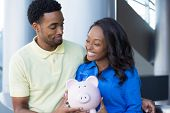 foto of borrower  - Closeup portrait happy handsome couple or two business people holding pink piggy bank looking at each other laughing - JPG