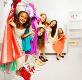 stock photo of clothes hanger  - Hiding girls during shopping choose clothes while standing among hangers with colorful bright dresses and children clothes in the store - JPG