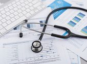 picture of stethoscope  - Stethoscope with financial on the desk - JPG
