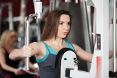 stock photo of health center  - Girl in sportswear exhales while doing exercises for arms and shoulders on training apparatus in fitness center - JPG