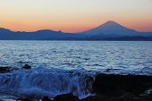 foto of mount fuji  - Mount Fuji silhouette at sunset. Ocean waves in foreground.