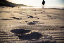 picture of footprint  - Footprint in the sand and the figure of a man cultivating Nordic walking - JPG