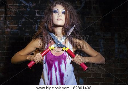Scary bloody woman with a secateurs in hand